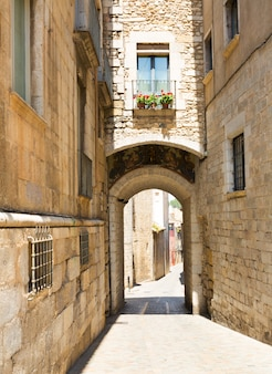 都市の古い狭い通りの上のアーチ。ジローナ