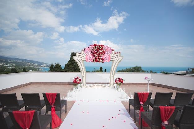 Арка красная для свадебной церемонии в море. гора.