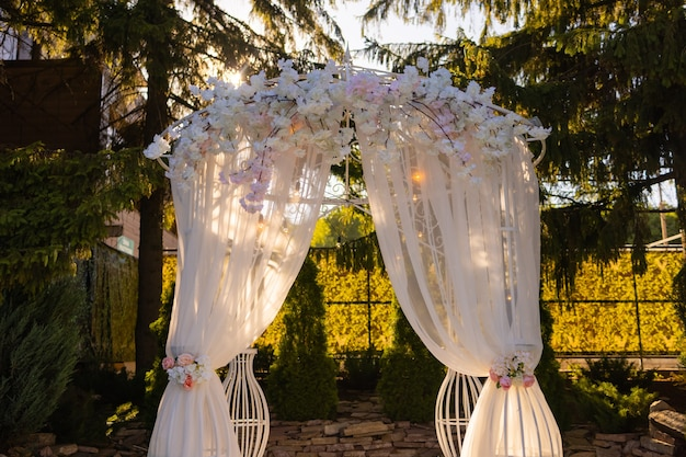 Arch for the wedding ceremony decorated with cloth flowers and greenery is in a pine forest