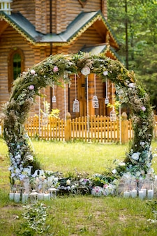Arch for the wedding ceremony. decorated with fabric flowers and greenery. is located in a pine forest.