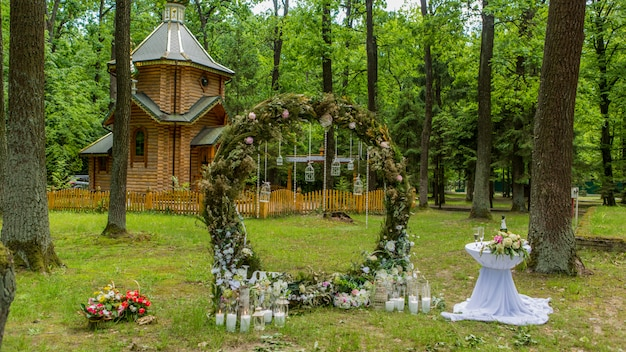 Arch for a wedding ceremony in a pine forest. church. candles in decorated jars. newlyweds. wedding decorations.