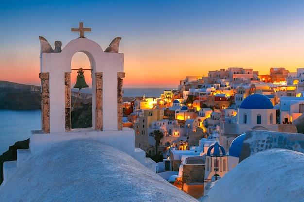 Арка с колоколом, белые дома и церковь с синими куполами в ия или иа на закате, остров санторини, греция