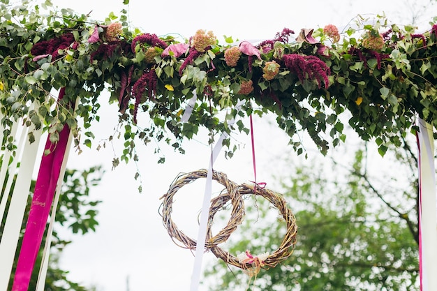 Arch with flowers ribbons and wedding rings from the branches close up wedding