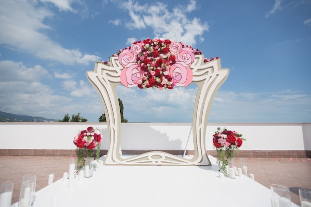 Arch with fresh red flowers on a background of sea and blue sky
