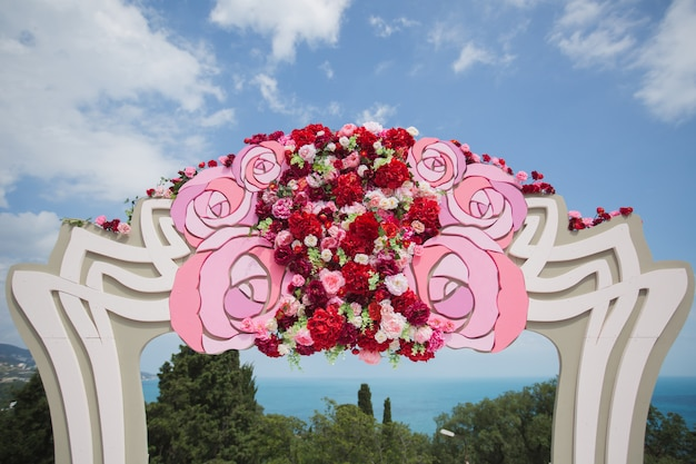 Arch with fresh red flowers on a sea and blue sky