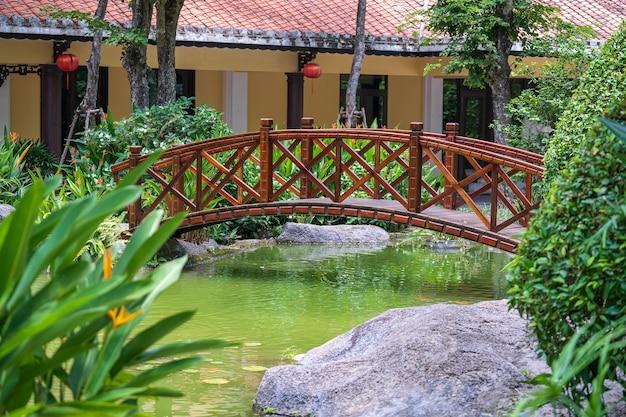 ベトナムのダナンにある日本のトロピカルガーデンの装飾的な池を通るアーチ橋。旅行と自然の概念