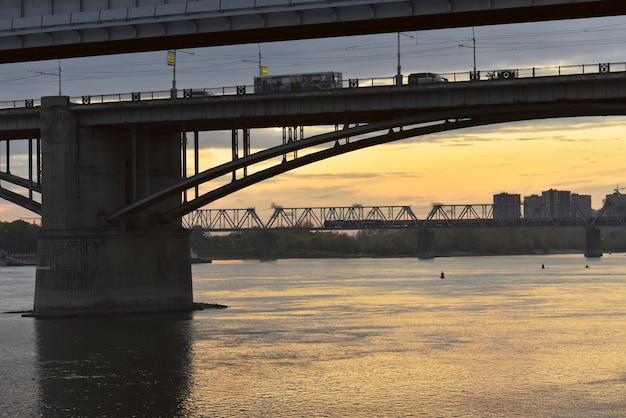 Arched road bridge railway bridge over the ob river in the capital of siberia