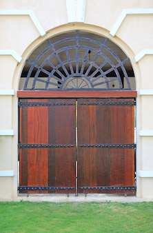 Arched wooden gate on cement wall.