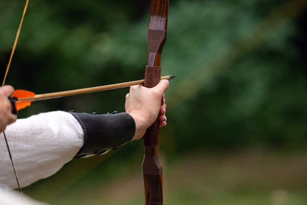 Лучник держит свой лук, целится в цель - соревнования по стрельбе из лука.