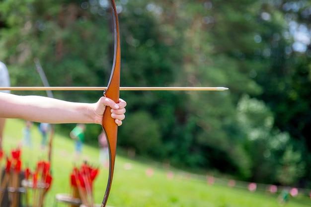 Арчер держит лук, целится в цель на свежем воздухе.