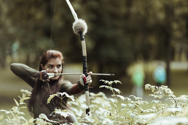 Archer woman shooting the bow and arrow in the swamp.