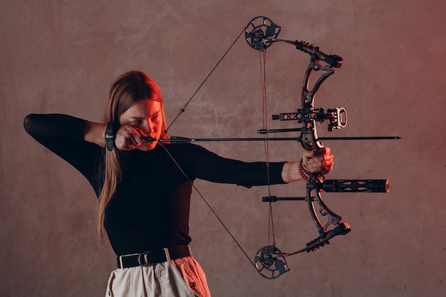 Archer woman with bow and arrow aims to target