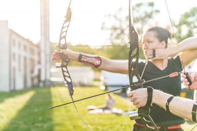 アーチェリーの競争、ターゲットをヒットする弓と矢を準備する女性