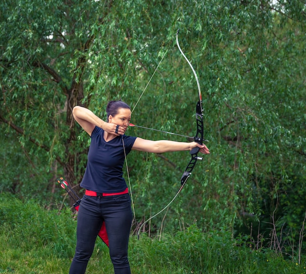 자연의 양궁. 매력적인 젊은 여자가 숲에서 대상에 화살표가 활 활 훈련