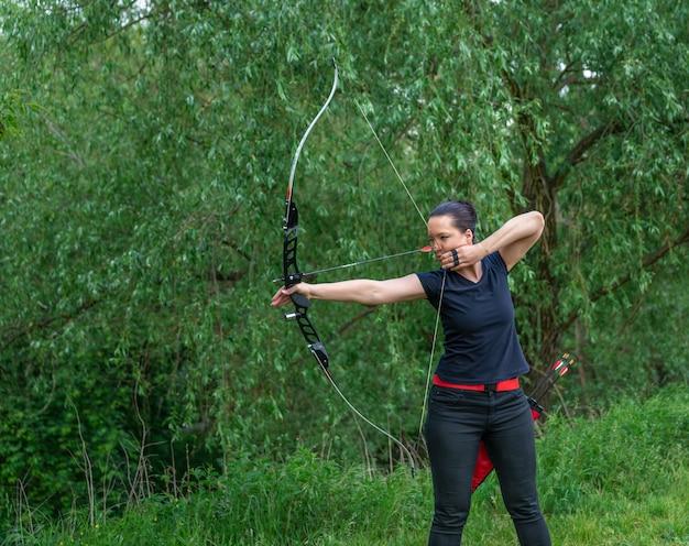 自然の中のアーチェリー。若い魅力的な女性が森の中でターゲットに矢でボウショットでトレーニング