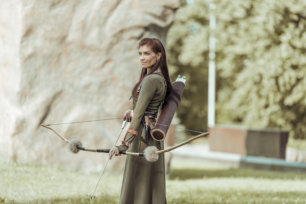 Archery woman with bow shooting on the forest