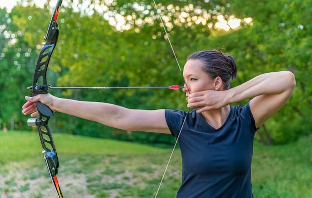 활에 화살을 가진 양궁, 젊은 여자는 목표물 타격에 집중