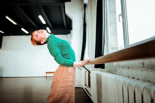 Арка возле балетного бара. молодой профессиональный артист балета с пучком волос делает изгиб, стоя возле балетного бара