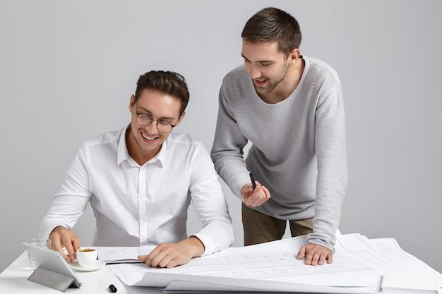 建築家の男性労働者が職場に集まり、現代の電子機器と青写真に囲まれています