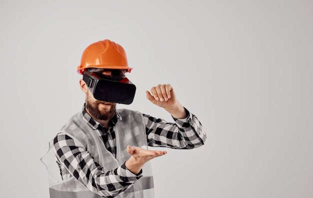 An architect in 3d virtual reality glasses gestures with his hands and an orange helmet on his head. high quality photo