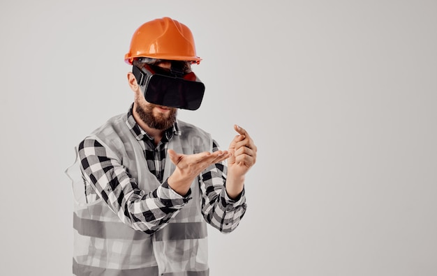 An architect in 3d virtual reality glasses gestures with his hands and an orange helmet on his head