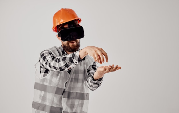 An architect in 3d virtual reality glasses gestures with his hands and an orange helmet on his head.