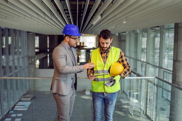 建築家と建設労働者は、建設過程で建物に立って、タブレットの青写真を見ています。