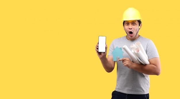 建築家アジア人の衝撃と黄色の壁に分離されたスマートフォンを提示する紙の家の形を保持している驚き