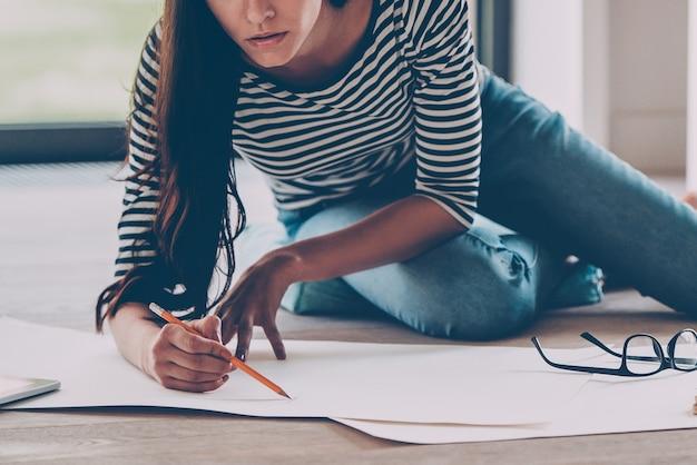 Архитектор за работой. крупный план уверенной в себе молодой красивой женщины, рисующей что-то на чертеже, сидя на полу дома