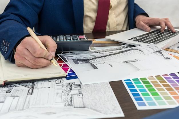 建築家は、ラップトップとカラーサンプルを使用して部屋のインテリアの装飾を構築するための色を選択します。カラーパレットと家のスケッチを扱うインテリアデザイナー