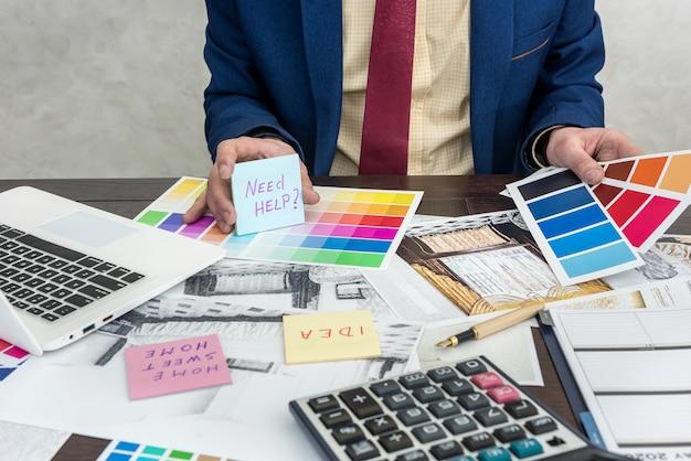 노트북 및 색상 샘플로 실내 장식을 구축하기 위해 색상을 선택하는 건축가. 색상 팔레트 및 하우스 스케치 작업 인테리어 디자이너
