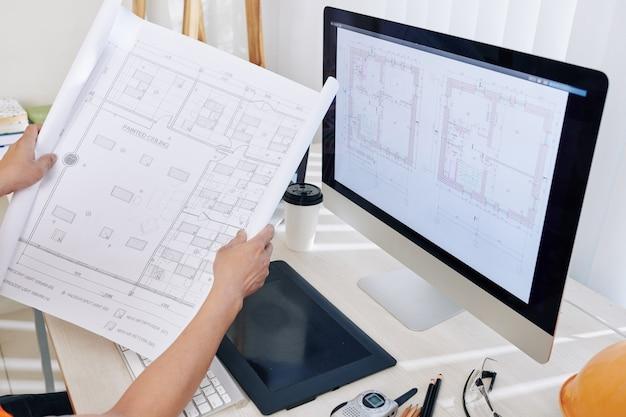 Architect comparing blueprints
