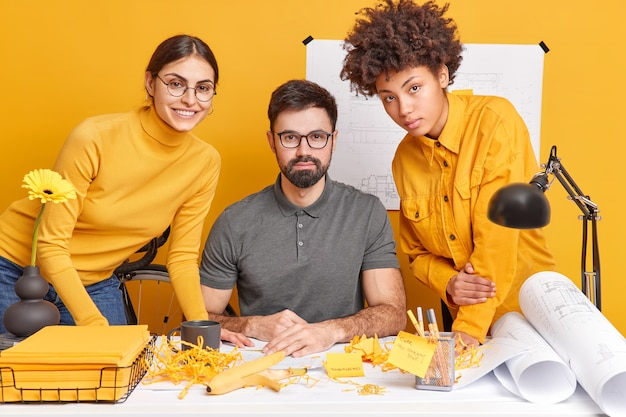 Architect coworkers collaborate together to finish work on blueprints pose at messy desktop share ideas with each other. three creative diverse people meet in office prepare future project or task