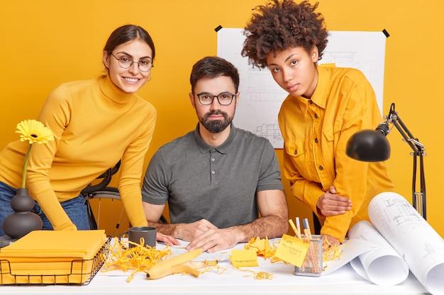 Коллеги-архитекторы вместе завершают работу над чертежами, позируют на грязном рабочем столе, обмениваются идеями друг с другом. три творческих разных человека встречаются в офисе, готовят будущий проект или задание.