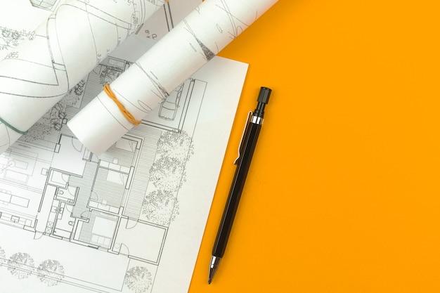 建築家のデザインコンセプト。スケッチ計画と青写真を描くデスクトップ。オレンジ色の背景、コピースペース、上面写真
