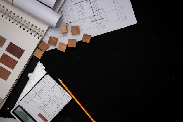 Architect designed the building in the design office, the floor plan with catalogs decorative materials and other accessories on the black wooden table.