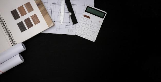 Архитектор спроектировал здание в конструкторском бюро, план этажа с каталогами декоративных материалов и других аксессуаров на черном деревянном столе.
