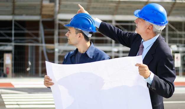 Architect developers reviewing building plans at construction site