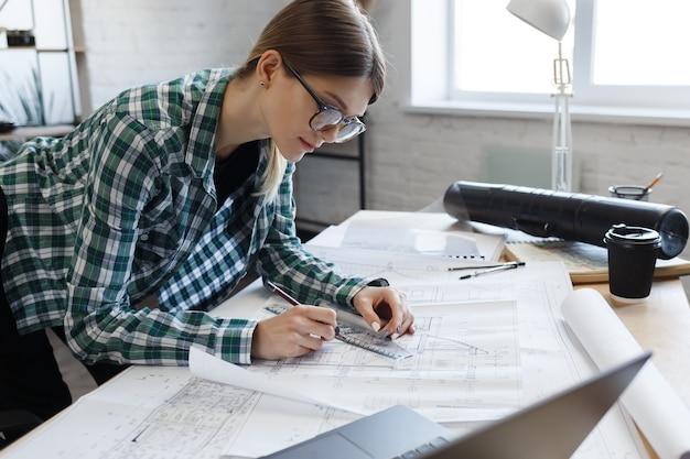 Архитектор рисует чертежи в офисе. инженер делает набросок архитектурного плана строительного проекта ...