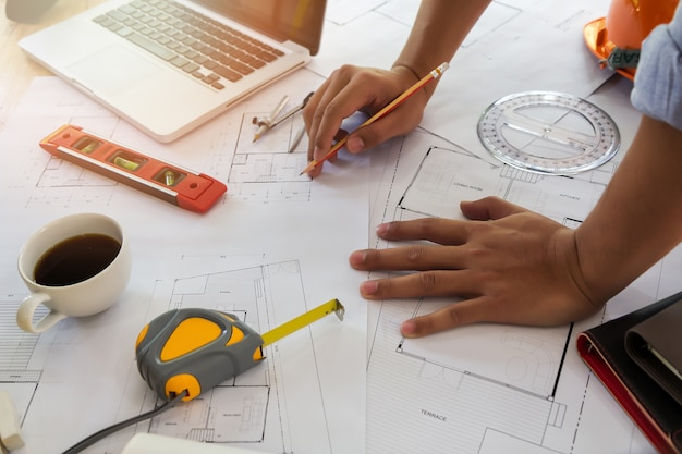 Architect or engineer working on blueprint in office, architectural concept