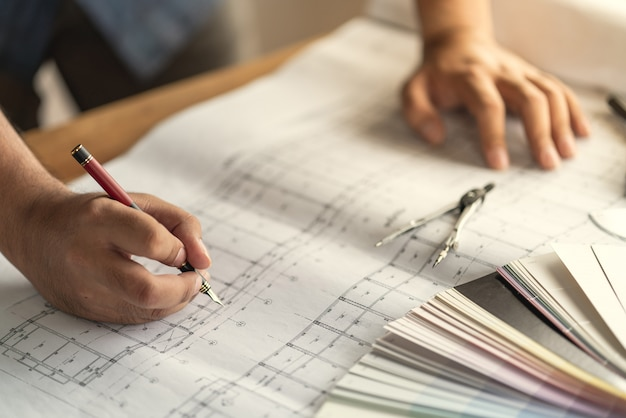 Architect & engineer working drawing document about project planning and progress of work schedule on the home building construction site