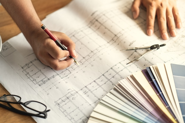 Architect & engineer working drawing document about project planning and progress of work schedule.