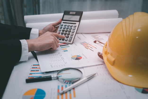 Architect or engineer working project accounting with graph and construction helmet in office.