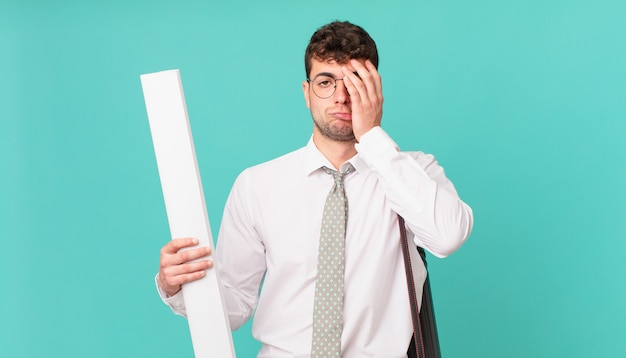 Архитектор чувствует скуку, разочарование и сонливость после утомительной, скучной и утомительной работы, держа лицо рукой