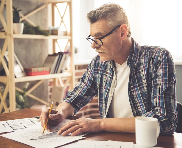 Architect in glasses is working with drafts in office
