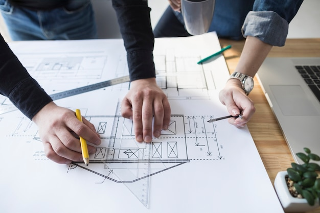 Architect hands working on blueprint on wooden desk at office