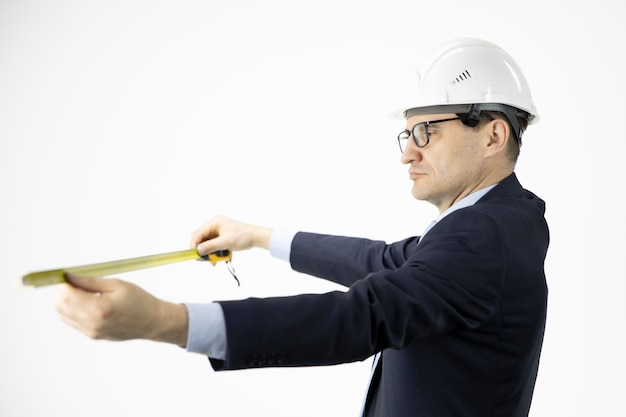 Architect in hard hat measures with tape measure on isolated white background