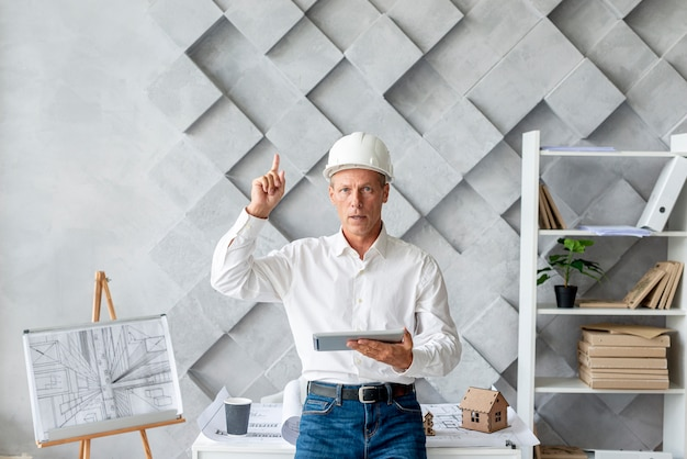Architect in his office pointing up