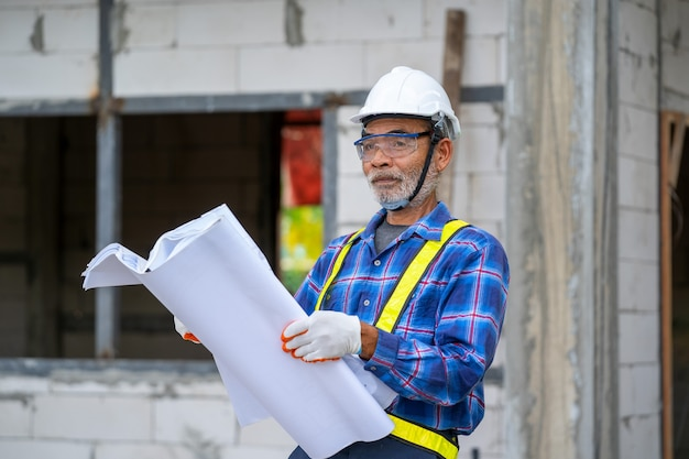 Architect holding blueprint in his hand checking the building under construction