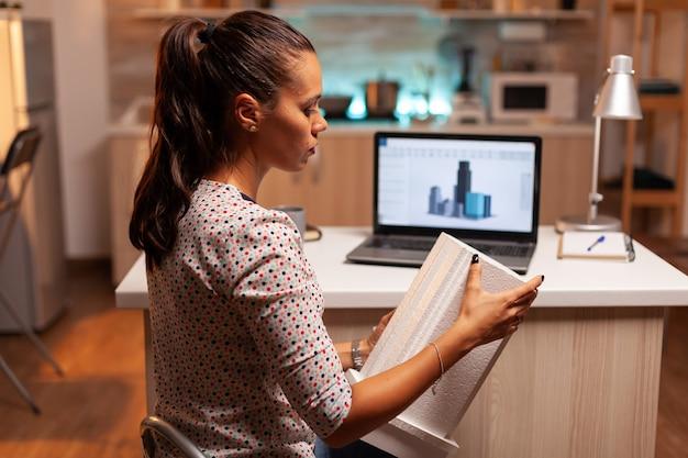 Архитектор держит модель здания во время работы над проектом в ночное время дома. инженер-художник, создающий и работающий в офисе, холдинг макет масштабного здания, определение, карьера.